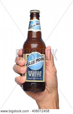 IRVINE, CALIFORNIA - APRIL 26, 2019: Closeup of a hand holding a bottle of  Blue Moon Belgian White Ale from Tenth and Blake Beer Company, the craft import division of Chicago-based MillerCoors.