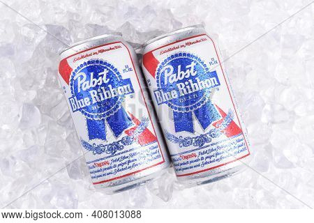 IRVINE, CALIFORNIA - MARCH 16, 2017: Pabst Blue Ribbon Beer. Two cans of the American brand on a bed of ice, introduced in 1884 in Milwaukee, currently based in Los Angeles.