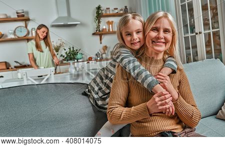 My Loving Grandmother. The Little Girl Hugs Her Grandmother And Laughs. On The Back Background Mom P