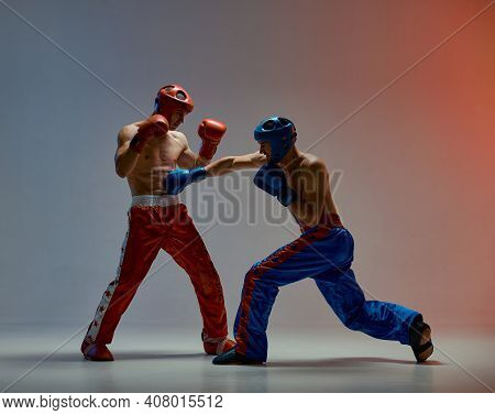 Fighting Guys During Boxing Fight Workout. Athletic Males In Boxing Gloves Training Martial Arts Tec