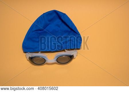 Professional White Glasses For Swimming And Blue Swimming Cap . White Swim Goggle Isolated On Yellow