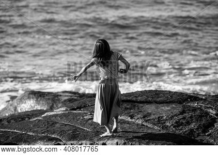 A young dance woman is engaged in choreography on the ocean coast. Black and white photo.