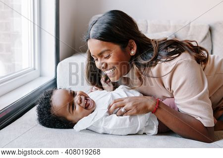 Happy Smiling Laughing Indian Mother Playing With Black Baby Girl Daughter. Family Mixed Race People