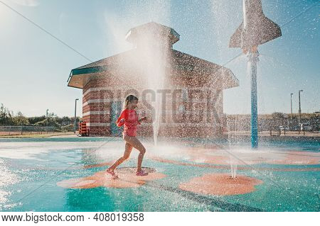 Cute Adorable Caucasian Funny Girl Playing On Splash Pad Playground On Summer Day. Happy Child Havin