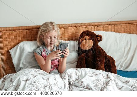 Cute Girl Sitting In Bed In Morning And Texting Talking At Social Media On Smartphone Cellphone. Chi