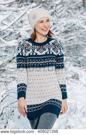 Middle Age Woman In Woollen Dress With Ethnic Pattern And Hat Walking In Park Outdoor On Snow Sunny