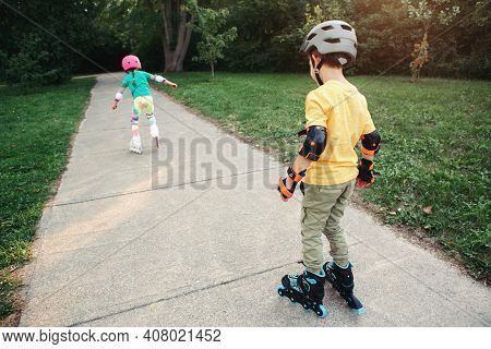 Friends Boy And Girl In Helmets Riding On Roller Skates In Park On Summer Day. Sister Encourage Stim
