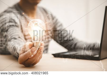 Business Hand Holding Light Bulb And Working With Computer On The Desk, Creativity And Innovation Ar