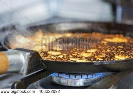 Making Pancakes On Frying Pan. The Process Of Cooking Pancakes On A Hot Frying Pan On Gas Stove Rang