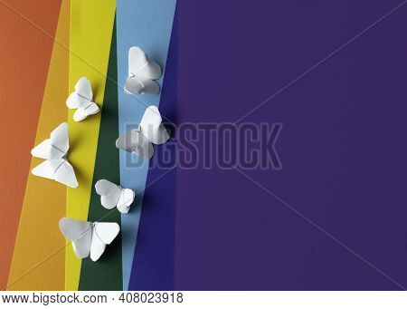 Rainbow Paper Background With White Paper Butterflies Origami. Zero Discrimination Day Concept. Copy