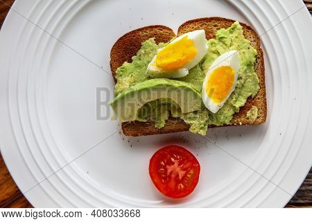 Toast with avocado and eggs on plate from above