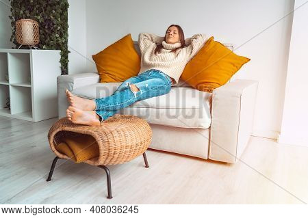 Calm Satisfied And Relaxed Woman In Cozy Sweater Resting Or Sleeping On The Sofa In The Living Room.