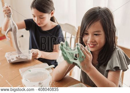 Happy Mixed Asian Girl Friends Making Homemade Slime Toy, Sensory Art And Craft, Fun Homeschool Chem
