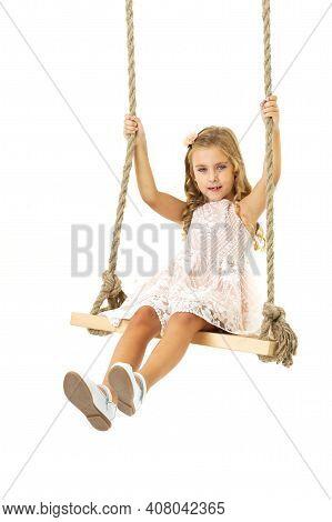 Beautiful Girl Swinging On Wooden Swing. Lovely Blonde Girl Swinging High Against White Background.
