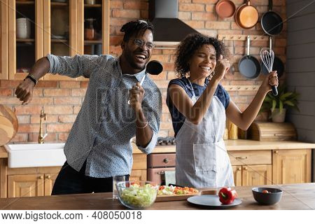 Close Up Overjoyed African American Couple Singing Into Kitchenware