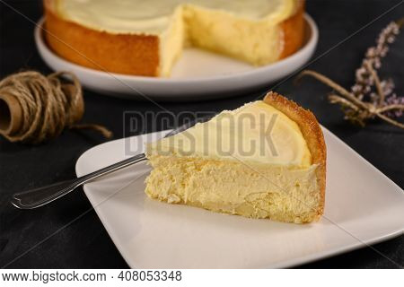 Slice Of Traditional New York Cheesecake With Cream Cheese And Sour Cream Layer On White Plate