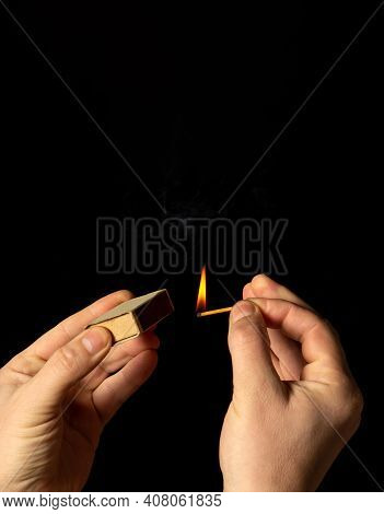 Hands Holds Burning Match On A Black Background. A Wooden Match Burns In The Hands Of Macro. Ignitin