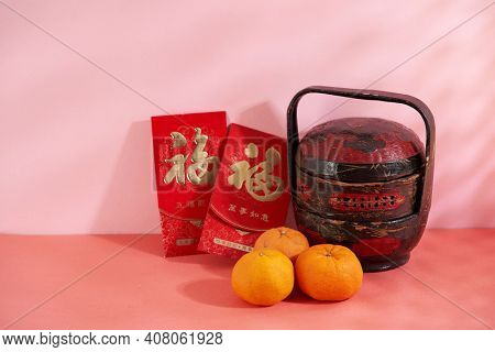 Lunar New Year  Orange in wood basket with red pocket money and flower. translation on red packet prosperous and everything go as your wish