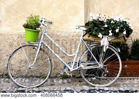 Finalborgo (sv), Italy - December 12, 2017: A White Bicycle Whith Flowers In Finalborgo Village, Fin