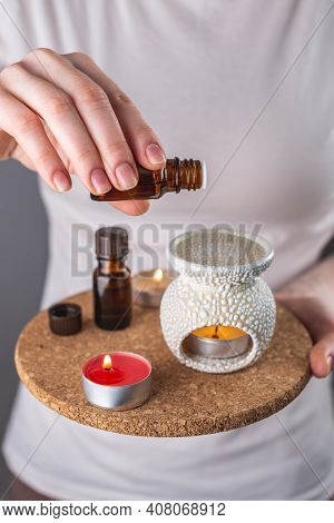 A Woman Is Dripping Organic Essential Oil Into An Aroma Lamp For A Relaxing And Pleasant Aromatherap