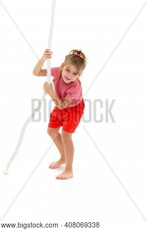 Active Happy Girl Hanging On Swing Rope. Kid Playing And Having Fun Doing Activities. Happy Smiling