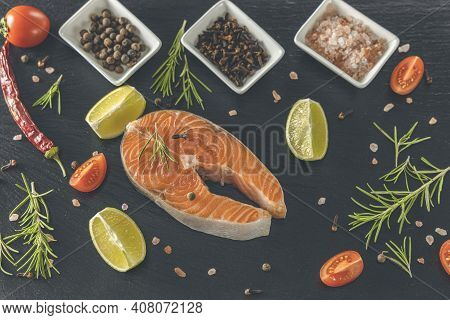 Raw, Fresh Salmon Steak On A Slate Board And Salt, Peppers, Lemon, Cloves And Rosemary Around. Raw S