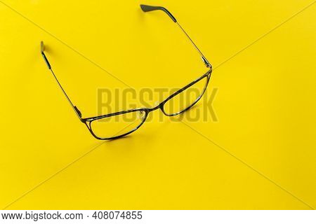 Stylish Glasses On A Yellow Background. Health, Style And Business Concept. Eyesight Correction.