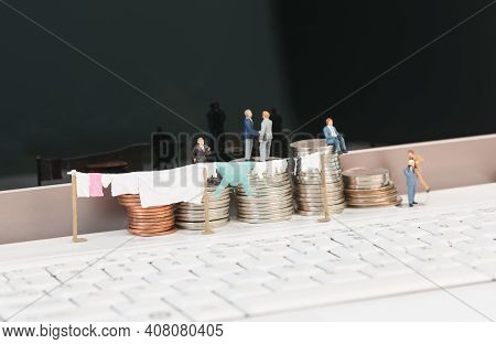 Money Laundering Concept With Miniature People, Clothesline And Coins