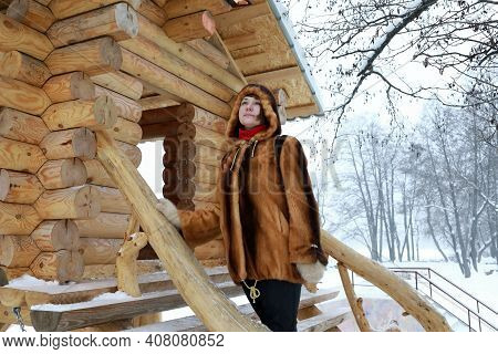 Woman Next To Log Cabin