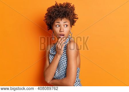 Portrait Of Shocked Afro American Looks Terrified Behind Back Notices Something Amazing Dressed In P
