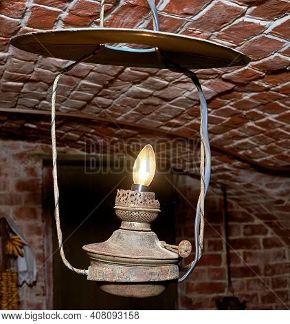 A Vintage Old-fashioned Steel Lamp. A Room In An Old House With Brick Walls