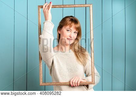 Beautiful Pretty Blonde Young Woman In Knitted Pullover With Loose Hair Holds Vintage Wooden Picture