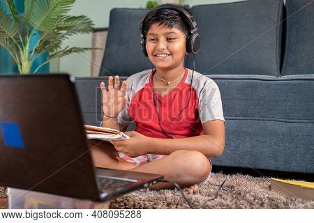 Young Kid With Headphones And Books In Handphone Greeting His Tutor During Online Class On Laptop At
