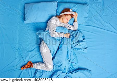 View From Above Of Redhead European Woman In Comfortable Pajama Rests On Soft Pillow Under Blanket A