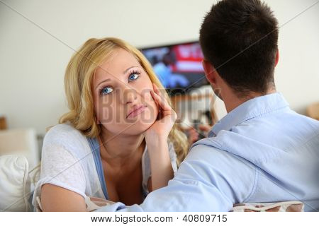 Blond woman being bored watching tv ith boyfriend