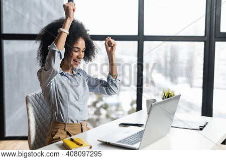 African-american Woman With Curly Hairstyle Hands Up, At The Desk With Open Laptop, Wide Smile, Exci