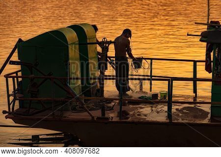 Monywa, Myanmar - December 22, 2019: View Of A Man Taking A Shower On His Boat Before Going To Home.