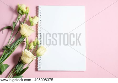 Delicate Eustoma Flowers On A Pink And White Background. Blank Notebook And Copy Space. Congratulato