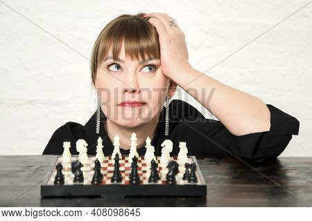 Beautiful Young Woman Is Looking Pensively Upwards While Sitting In Front Of Chessboard With Spaced