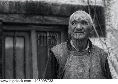 Stakna, India - August 26, 2015: A Senior Tibetan Monk With Wrinkled Face Looking Away At The Stakna