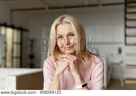 Elegant Middle-aged Woman With Blond Hair Sitting At The Camera, Looking At You, Smiling, Holding Ha