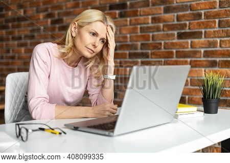 Discouraged Middle-aged Woman Sitting At The Laptop, Does Not Know What To Do, At Office, Looking At