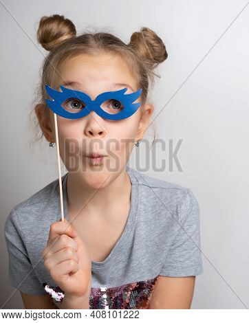 Little Girl With Wondered Facial Expression In Paper Eyeglasses Masquerade Mask Studio Portrait. Ama
