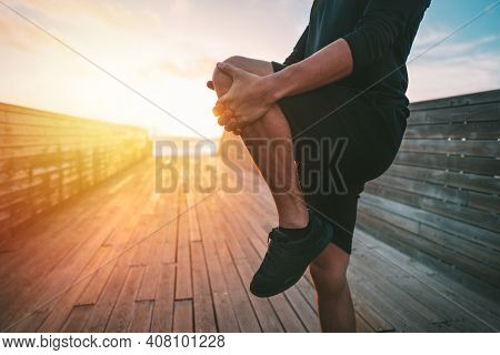 Healthy Young Man Warming Up And Stretching Legs Before Workout Outdoors At Sunset Or Sunrise. Stret