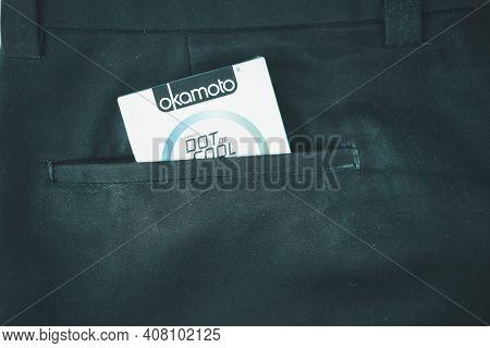 Samut Prakan, Thailand - February 15, 2021 : Box Of Okamoto Condoms In Black Slack Pants Pocket. Top