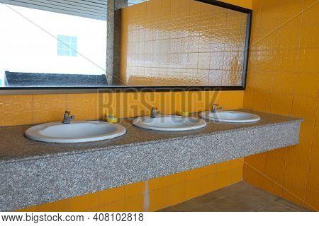 Interior Of Public Bathroom With Sink Basin Faucet.