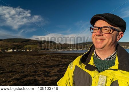 Middle-aged White Man Smiling On The Beach, Wearing Glasses, A Black Cap And Gill Yellow Gill Jacket