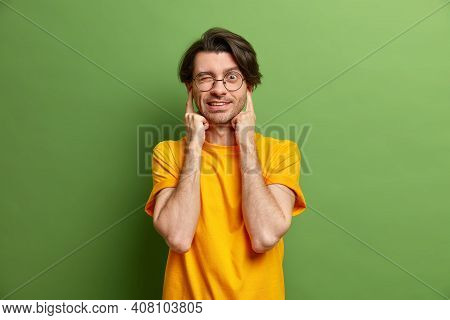 Handsome Man With Dark Hair Plugs Ears Winks Eye Avoids Loud Sound Wears Casual Yellow T Shirt Round
