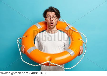 Horizontal Shot Of Shocked Young Man Beach Rescuer Poses Inflated Lifebuoy Keeps Mouth Opened Wears