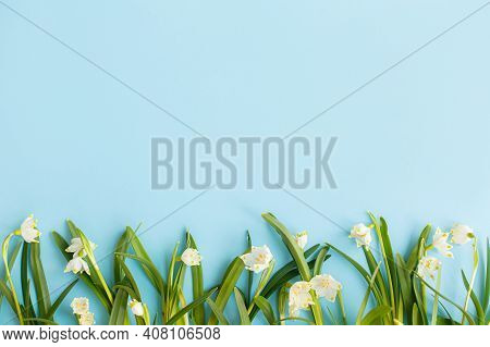 Spring Flowers Border On Blue Paper Flat Lay. Floral Greeting Card, Space For Text. Earth Day